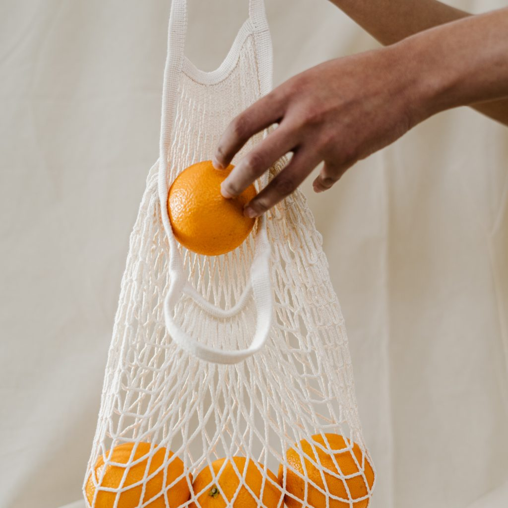 person-holding-orange-fruits-in-white-net-3737624